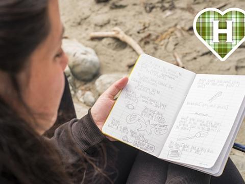 HSU student studies notebook on beach