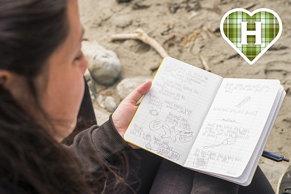 HSU student studies notebook on beach