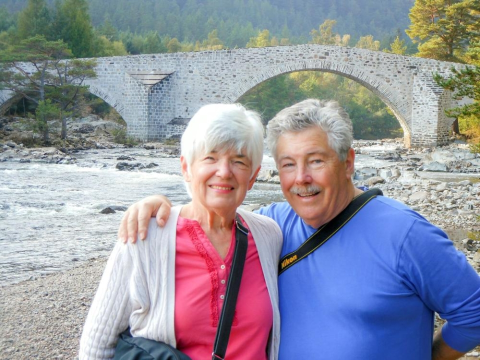 Jack and Diana McGurk standing in front of a bridge, next to a river